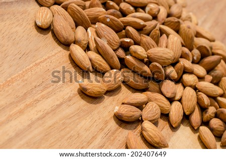 Pile of fresh almond nuts spread out on wooden surface - stock photo