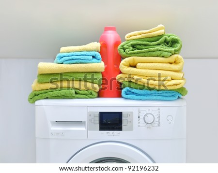 Pile of fresh colorful towels and bottle of detergent on washing machine - stock photo