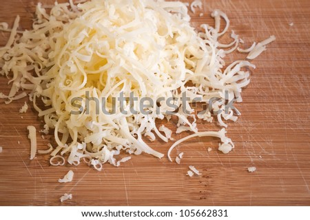 Pile of fresh grated cheese on wooden table - stock photo