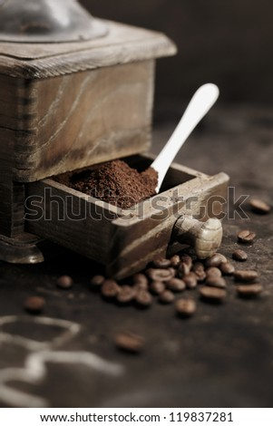 Pile of fresh ground coffee grains in the open drawer of an old rustic wooden coffee grinder with a measuring spoon in a country kitchen - stock photo
