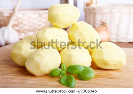 Pile of fresh potatoes with green leaves of basil