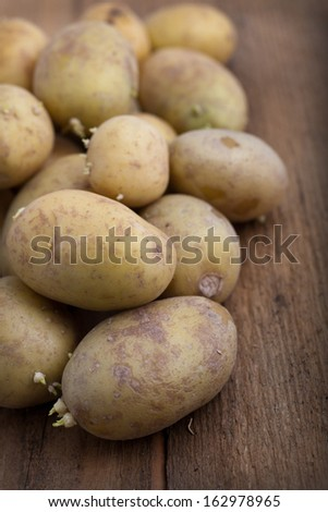 Pile of fresh raw potatoes on a wooden table, vertical format with shallow dof - stock photo