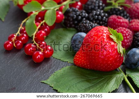 pile of fresh ripe berries with green  leaves   on black stone  - stock photo