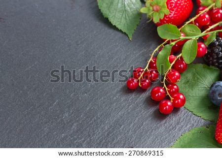 pile of fresh ripe berries with green  leaves with copy space   on black stone  - stock photo