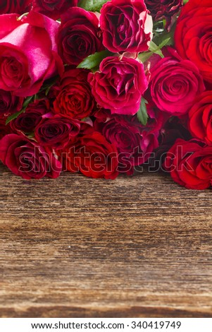 pile of fresh vivd red roses on wooden background