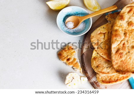 Pile of freshly baked flat bread and spices on a kitchen counter surface with Copy space - stock photo