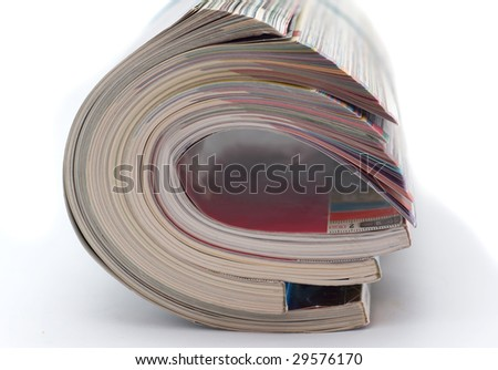 Pile of glossy magazines is curtailed into  roll isolated on white background - stock photo