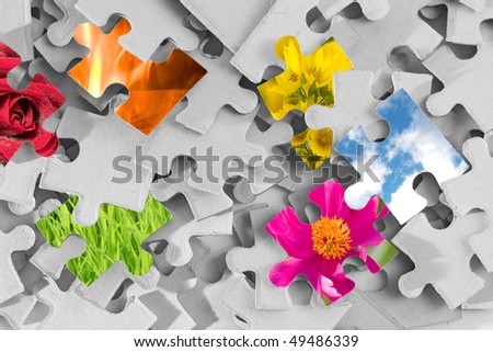 Pile of gray puzzle parts with several parts made as colorful images of nature - stock photo