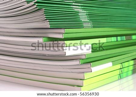 Pile of green magazines isolated on white background - stock photo