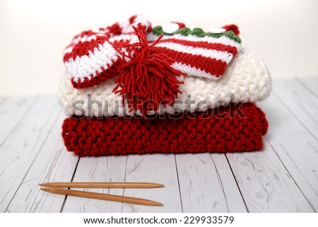 Pile of hand knit Christmas clothes - stock photo