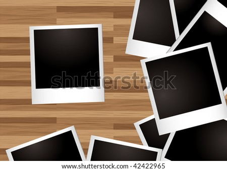 Pile of instant photographs spread on a wooden desk - stock photo