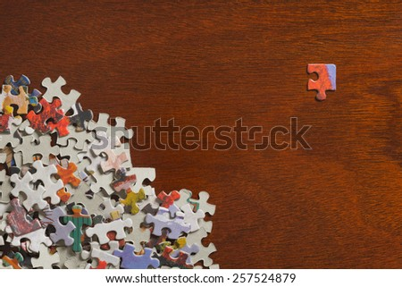 Pile of jigsaw puzzle pieces with a single corner piece separated on a dark wooden table top. - stock photo