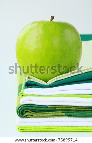 Pile of linen kitchen towels with green apple - stock photo