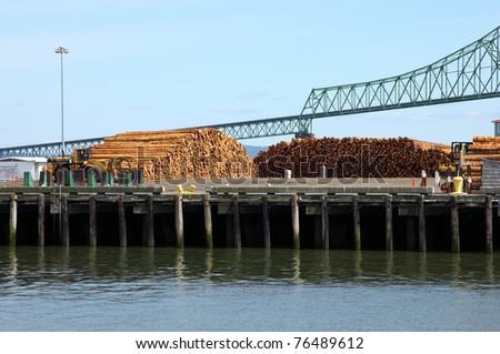 Pile of logs on decks & the Astoria bridge, OR. - stock photo