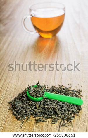Pile of loose leaf green tea with spoon on vintage wooden table