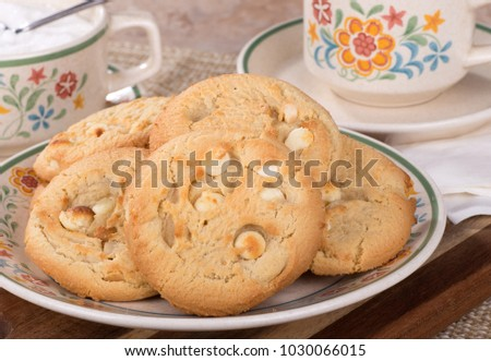 Pile of macadamia nut cookies on a plate with coffee cup and sugar bowl in background