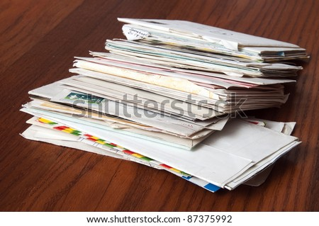 Pile of mails on wooden table - stock photo