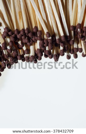 Pile of matches with dark brown heads isolated on white background