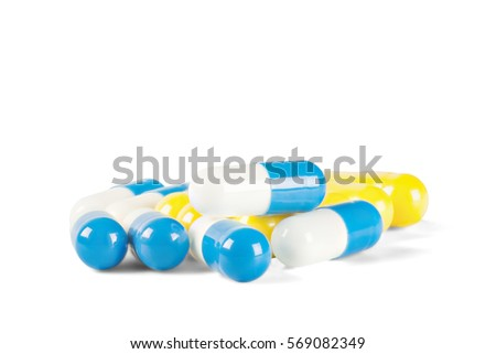 pile of medical pills blue and yellow color on isolated white background