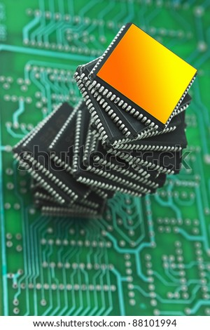 pile of microchips on a printed circuit board - stock photo