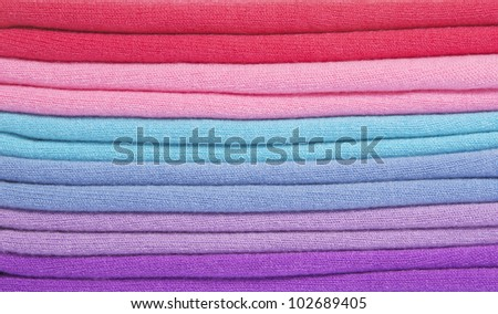 Pile of multicolored knitted clothes macro - stock photo