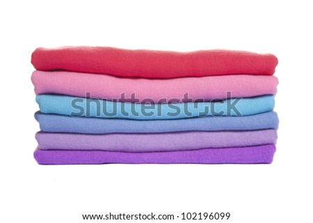 Pile of multicolored knitted clothes on white - stock photo