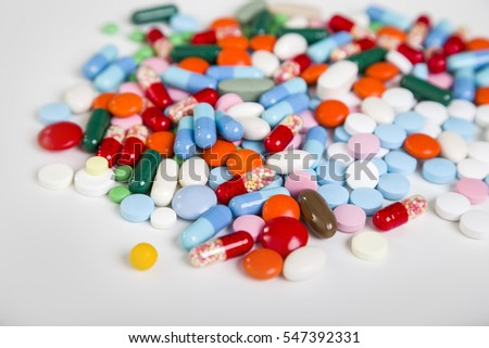 Pile of multicolored pills lying on a white surface. Close up. Conept of taking care and staying healthy