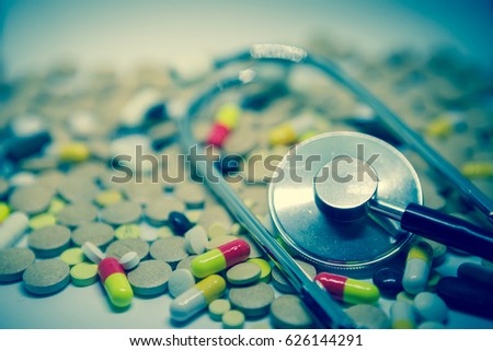 Pile of multicolored tablets and medicine lying on a white surface. Close up.   Selective focus/toned photo