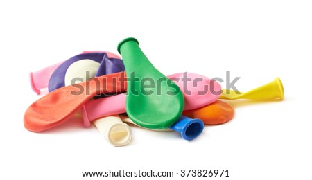 Pile of multiple colorful deflated rubber air balloons isolated over the white background