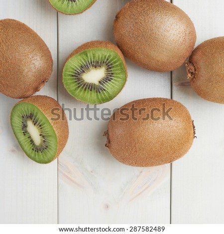 Pile of multiple kiwifruits or chinese gooseberries over the white colored wooden boards surface - stock photo