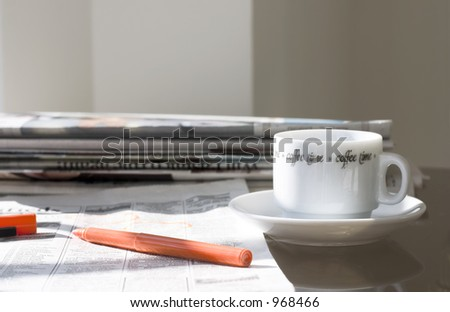 pile of newspapers, coffee cup and marker in the morning light - stock photo