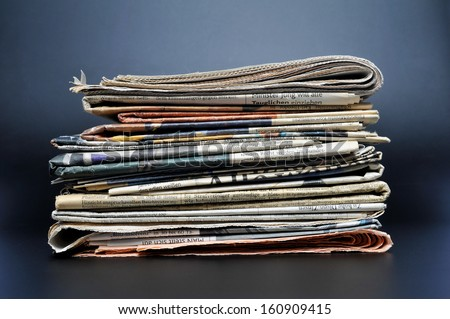 Pile of newspapers on black background - stock photo
