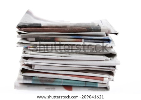 Pile of newspapers on plain background - stock photo