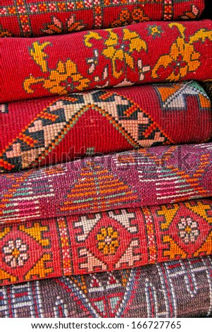Pile of north african rugs in red, orange & brown shades, Morocco. - stock photo