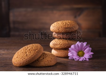 pile of oat cookies on wooden table with purple flower - stock photo