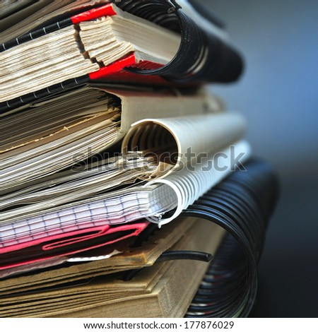 Pile of office binders on black background - stock photo