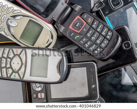Pile of old and used mobile phones - stock photo