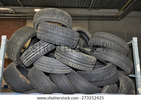 Pile of old black tires in a garage - stock photo