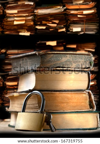 Pile of old books and keylock on archive folders background - stock photo