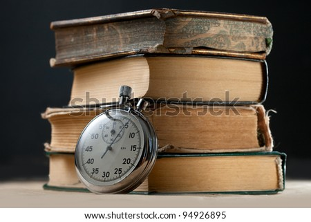 Pile of old books and stopwatch - stock photo