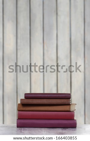 Pile of old books isolated on wooden background - stock photo