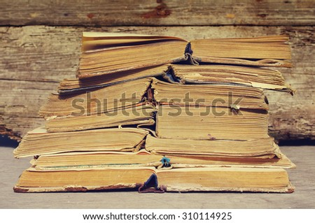 Pile of old books. Old open books against a wooden wall close up  - stock photo