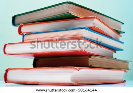 Pile of old books on light background. Shallow DOF
