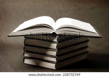 pile of old books on light table, one book opened, retro colors - stock photo