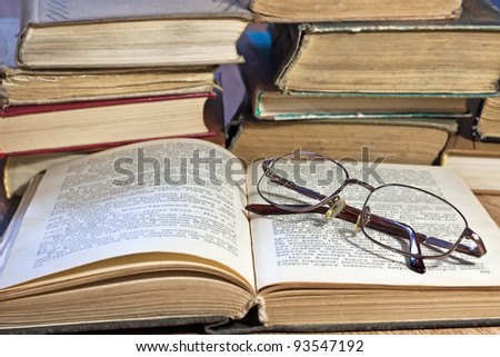 Pile of old books with glasses on wooden table
