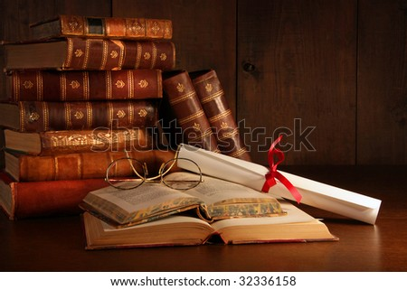 Pile of old books with reading glasses on desk - stock photo