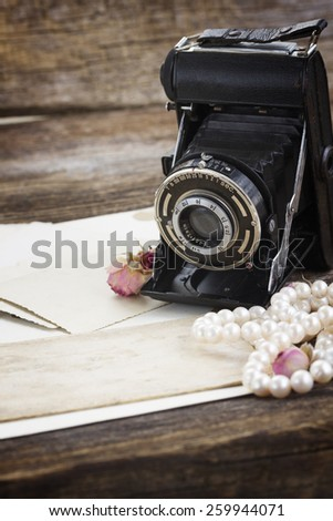 pile of old papers with vintage camera - stock photo