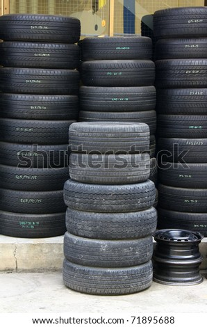 Pile of old tires and wheels for rubber - stock photo