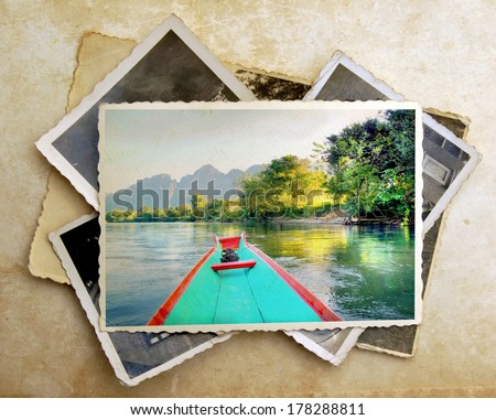 pile of old vintage photographs with on top a colorful image from a canoe on a river surrounded with amazing mountains  - stock photo