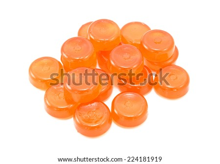 Pile of orange boiled sweets, or hard candies, isolated on a white background - stock photo